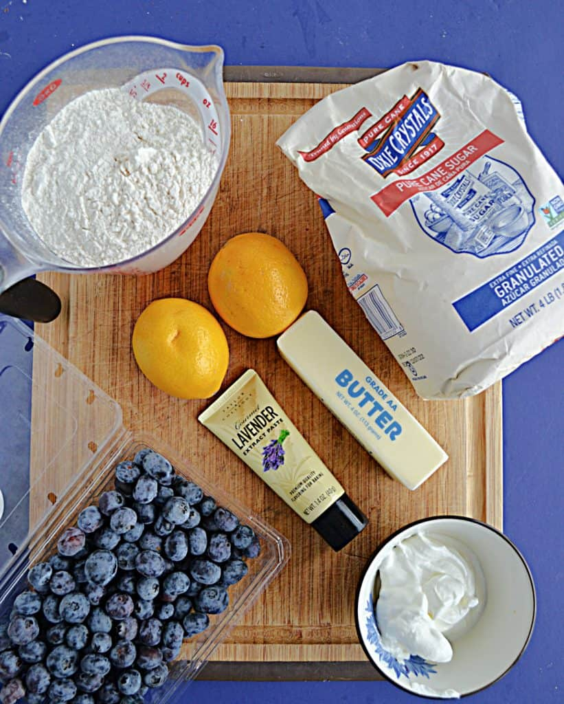 A cutting board topped with a cup of flour, a bag of sugar, 2 lemons, butter, lavender extract, a container of berries, and a bowl of sour cream.