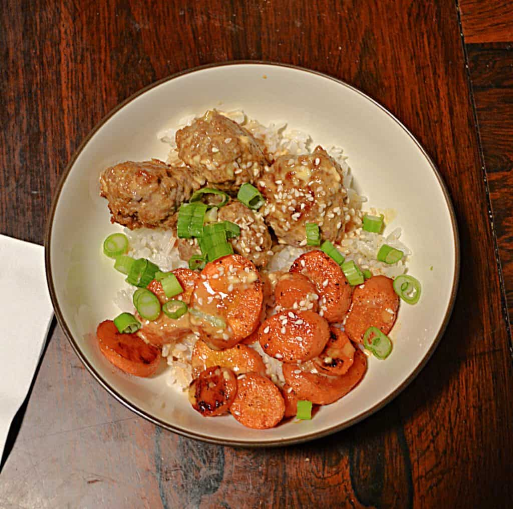 A bowl filled with rice, Firecracker meatballs, roasted carrots, and scallions.