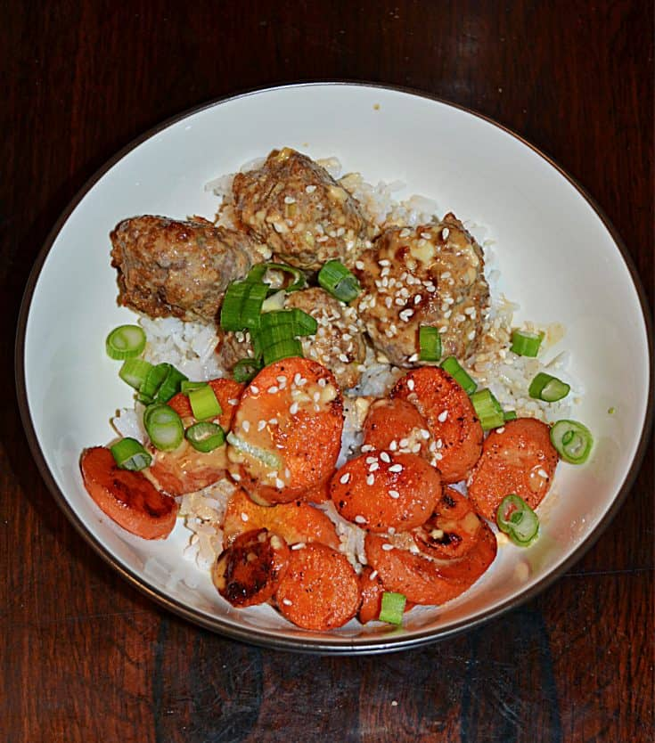 A close up of a bowl filled with rice, Firecracker meatballs, roasted carrots, and scallions.