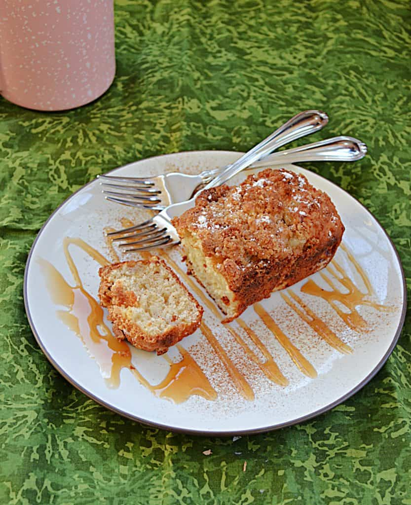A plate drizzled in caramel sauce topped with a pear ginger mini cake with two forks on the plate and a coffee cup in the background.