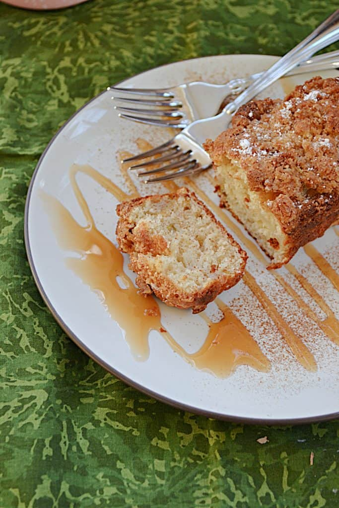 A close up of a plate drizzled in caramel sauce topped with a pear ginger mini cake with two forks on the plate