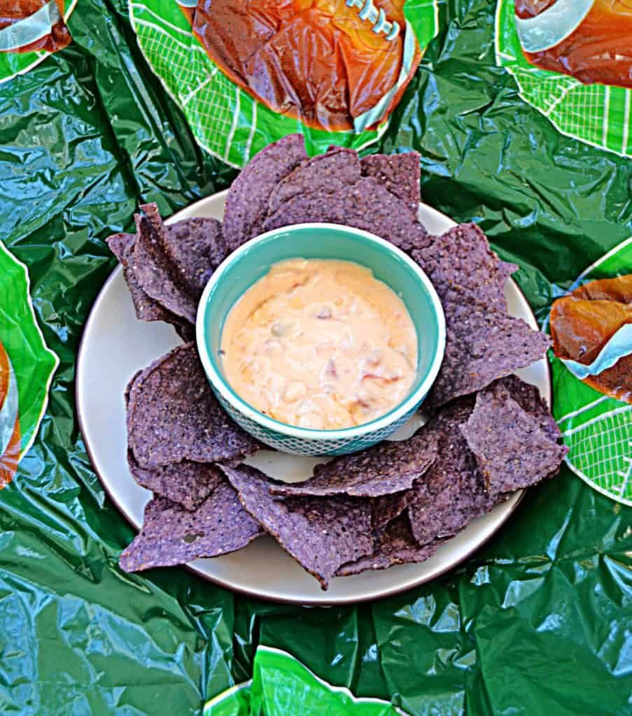 A plate of blue tortilla chips with a bowl of queso in the middle on a football background.