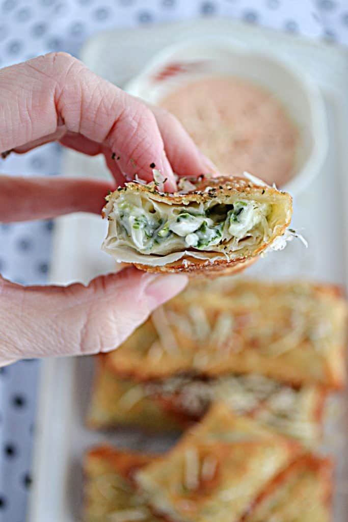 A close up view of a broken open egg roll with spinach artichoke dip in the center of it with a blurry background of more egg rolls and a bowl of spicy dipping sauce.