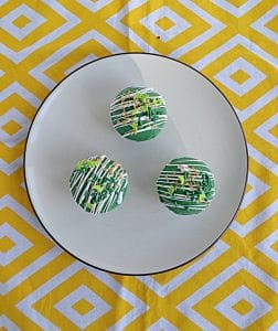 A plate with three green Hot Chocolate Bombs on it on a yellow background.