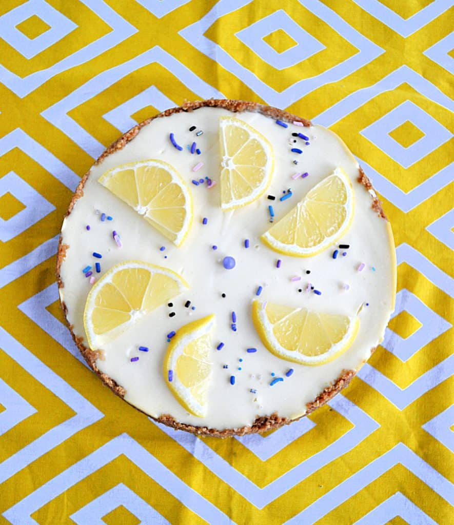A cheesecake topped with lemon slices and purple sprinkles.