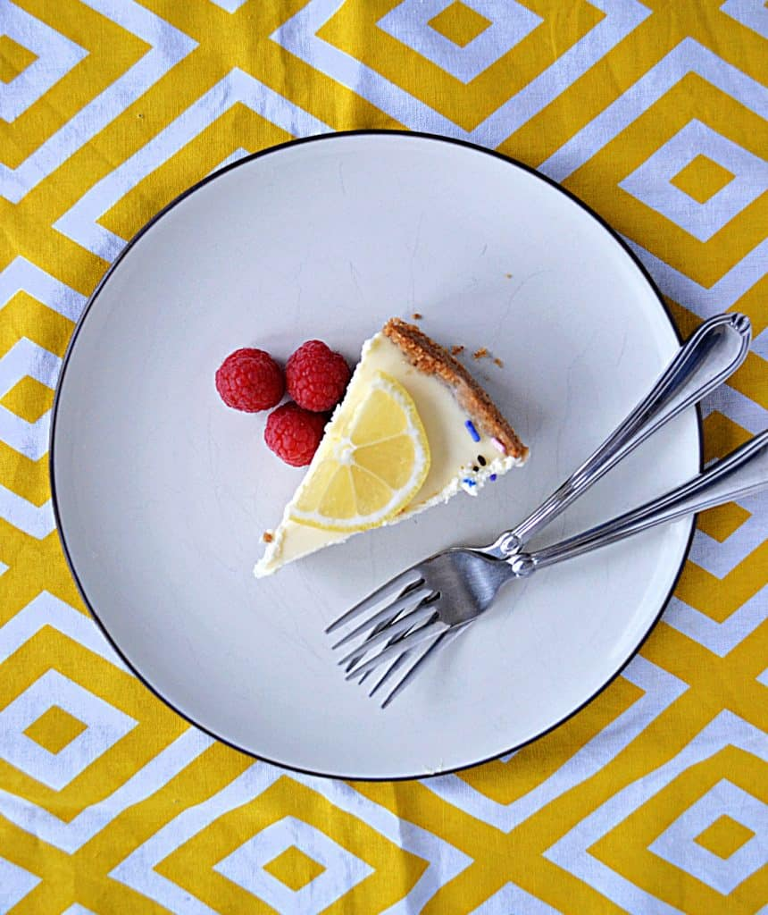 A plate topped with a sliced of lemon lavender cheesecake with a lemon slice on top, three raspberries on the side, and two forks on the plate.