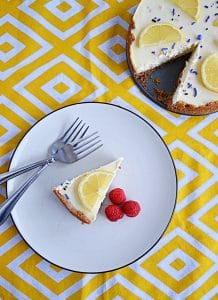 A top view of A plate topped with a sliced of lemon lavender cheesecake with a lemon slice on top, three raspberries on the side, and two forks on the plate with the cut cheesecake in the background.