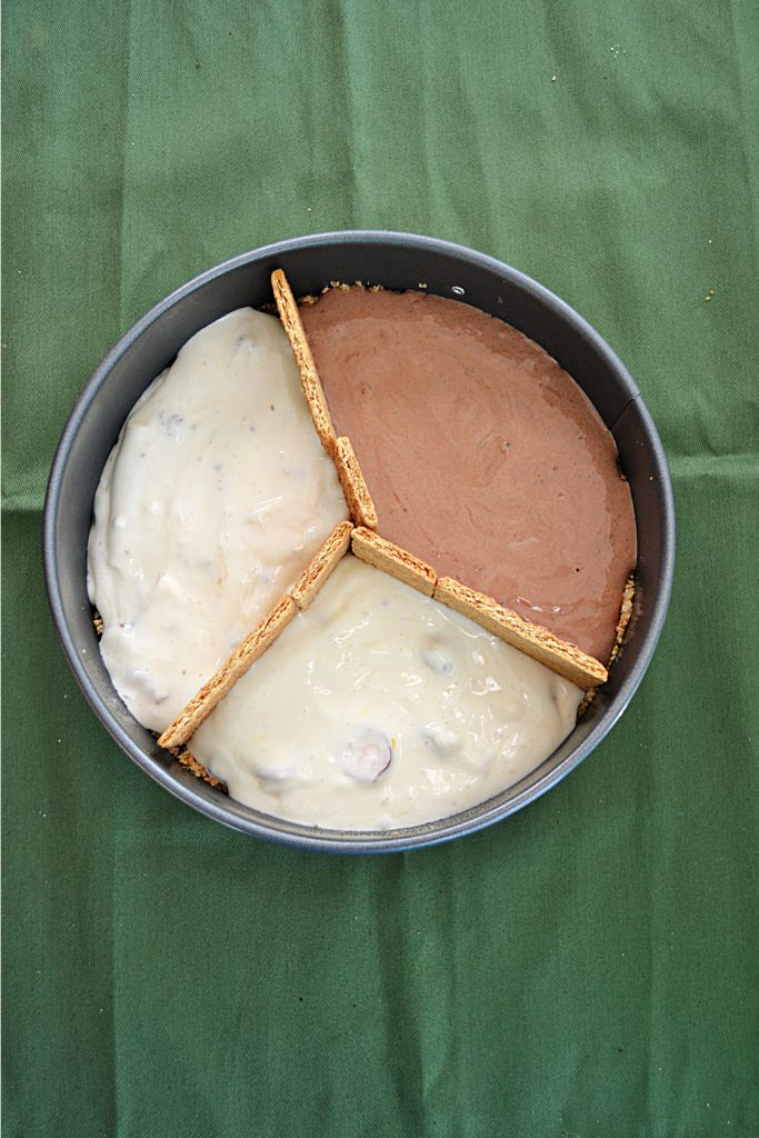 A cake pan with three different flavors of cheesecake divided by graham crackers.