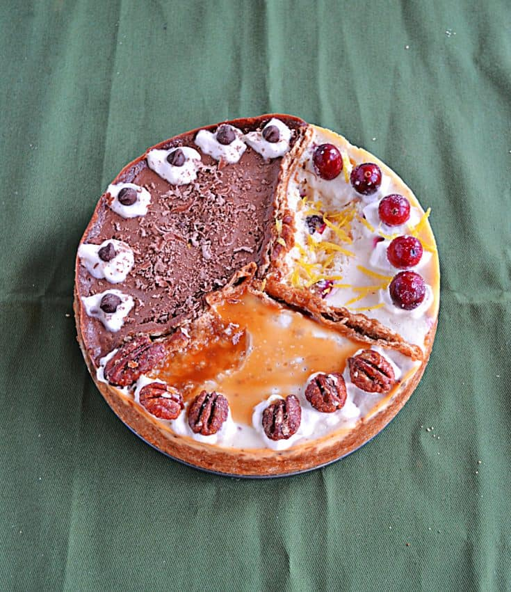 A cheesecake divided into 3 sections: One is orange cranberry with whole cranberries on top, one third is caramel pecan cheesecake topped with caramel and pecan halves, and one third is chocolate espresso topped with espresso beans.