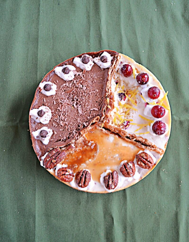A top view of a cheesecake divided into 3 sections: One is orange cranberry with whole cranberries on top, one third is caramel pecan cheesecake topped with caramel and pecan halves, and one third is chocolate espresso topped with espresso beans.