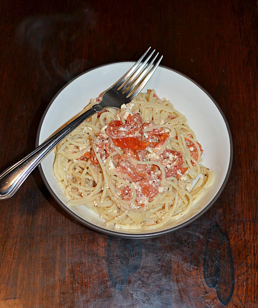 A bowl of spaghetti combined with tomatoes and feta with a fork sitting on top of the bowl.