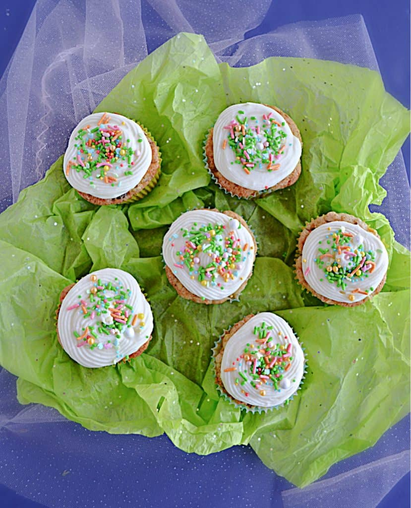 Six carrot cake cupcakes topped with cream cheese frosting and sprinkles on a green background.