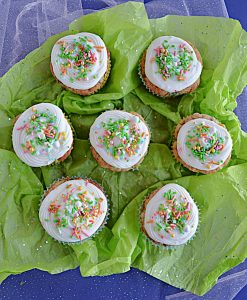 Top view of seven carrot cake cupcakes topped with cream cheese frosting and sprinkles on a green background.