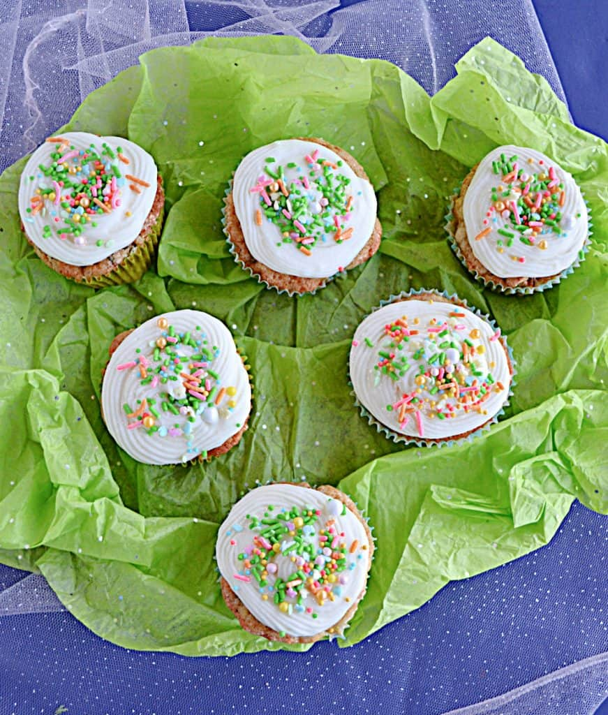 A pile of carrot cake cupcakes topped with cream cheese frosting and sprinkles on a green background.