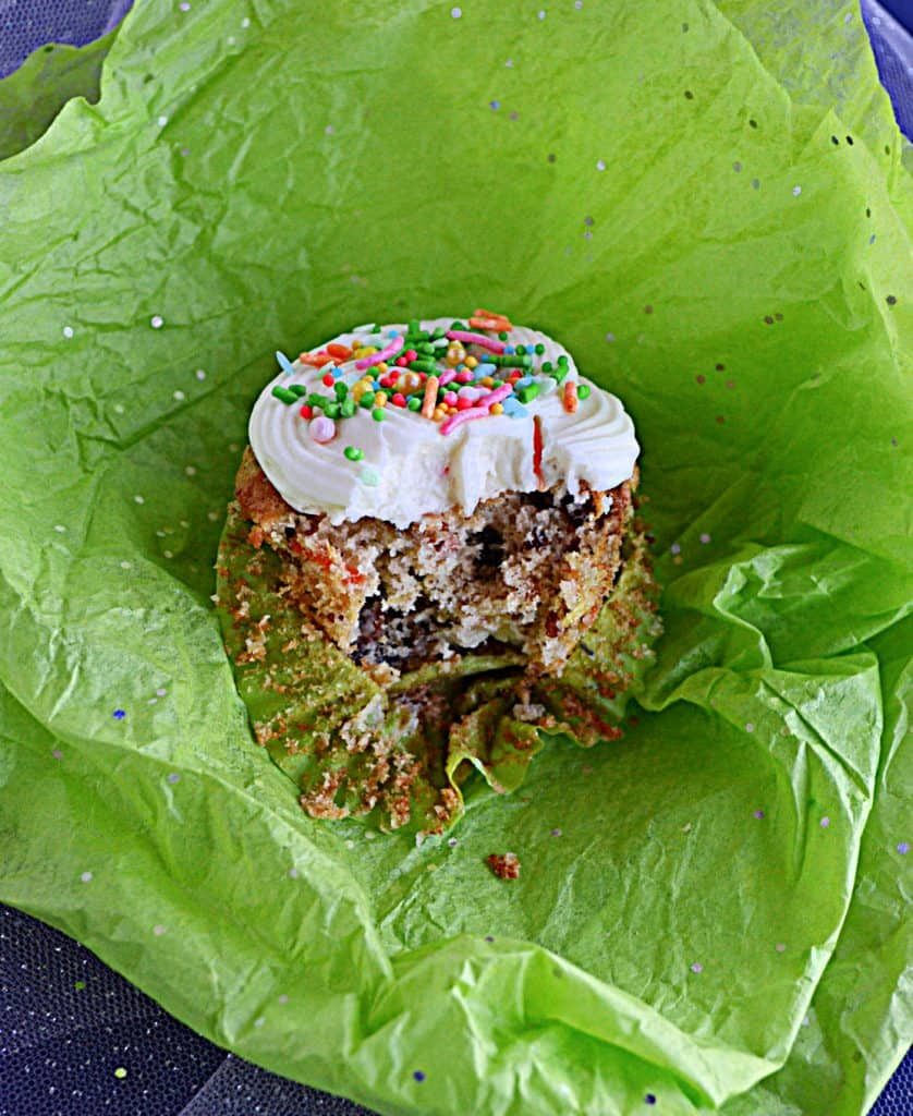 A carrot cake cupcake topped with cream cheese frosting and sprinkles with a big bite taken out of it sittin gon green tissue paper.