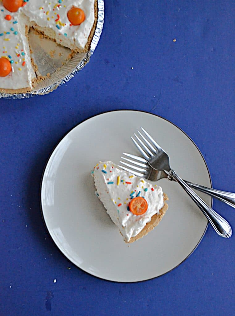 A top view of a slice of No Bake Kumquat Pie with a kumquat on top and two forks on the plate and the pie with a slice cut out of it in the upper left hand corner.