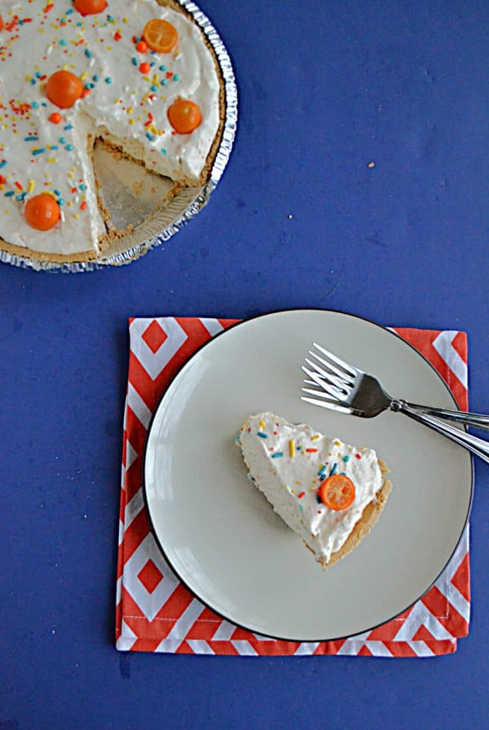 A slice of No Bake Kumquat Pie with a kumquat on top and the pie with a slice cut out of it in the upper left hand corner.