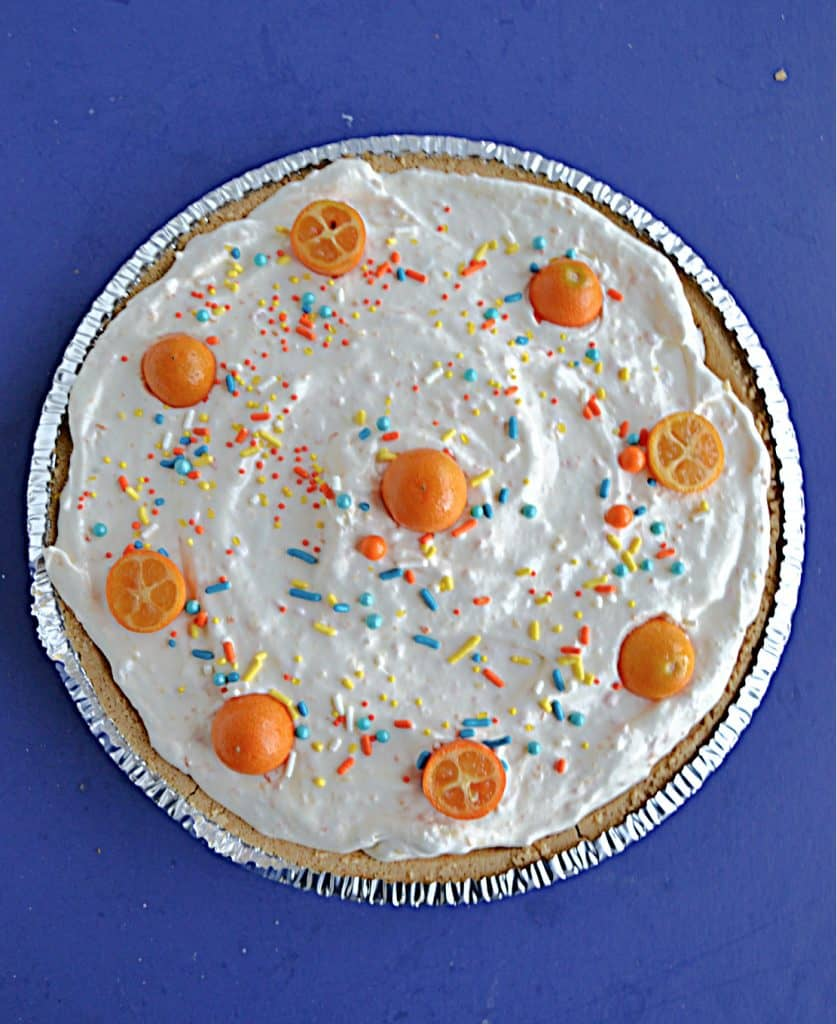 No Bake Kumquat Pie is topped with whipped cream and little kumquats and sprinkles.
