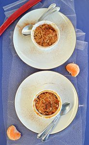 A top view of two plates with two ramekins on them with golden brown crumble on top each with two spoons on the plate with a stalk of rhubarb at the top and half an orange beside the plates.