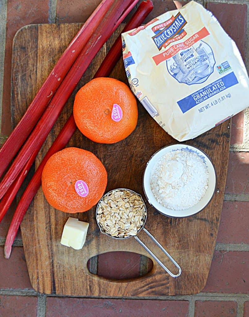A cutting board with 3 stalks of rhubarb, a bag of sugar, two oranges, a cup of oats, flour, and butter on it.