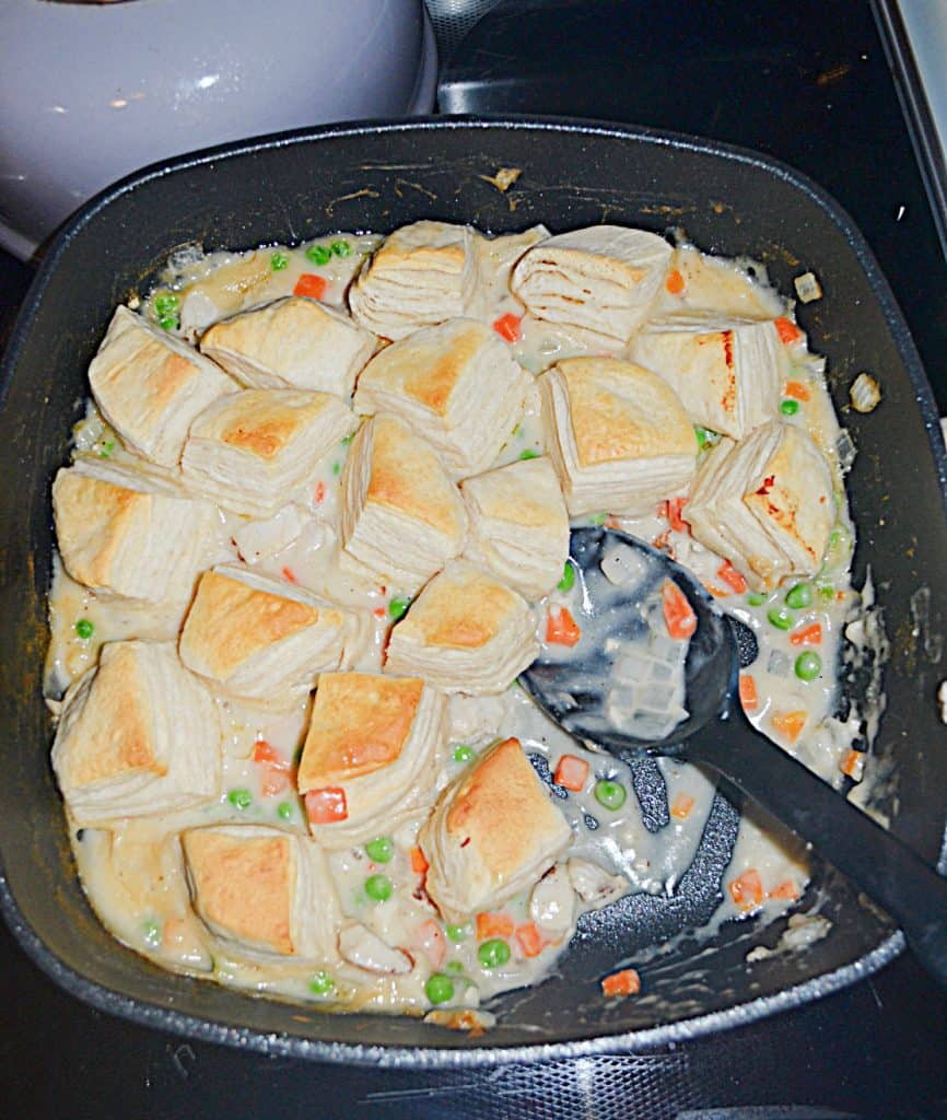 A pan of chicken pot pie topped with biscuits with a spoon in it.