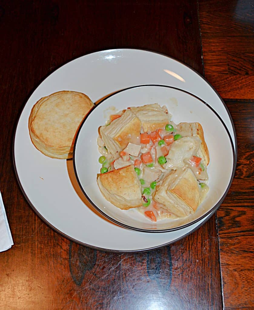 A bowl filled with chicken pot pie topped with biscuits with a biscuit on the side.