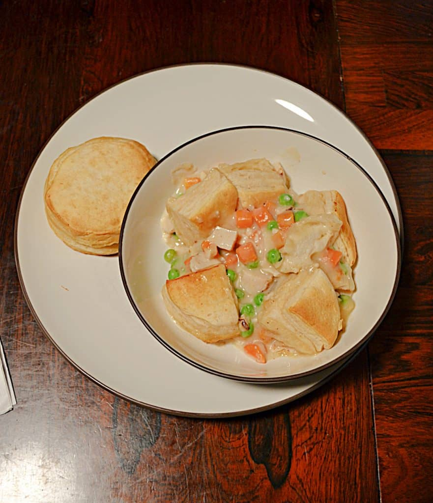 A top view of a bowl filled with chicken pot pie topped with biscuits with a biscuit on the side.