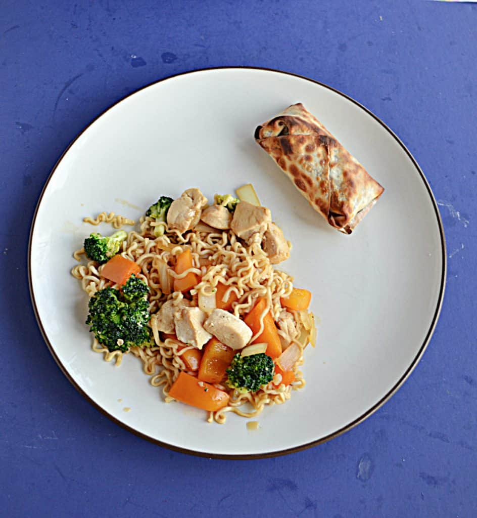 A plate with a large serving of chicken, vegetable, and ramen noodle stir fry with an egg roll on the side.