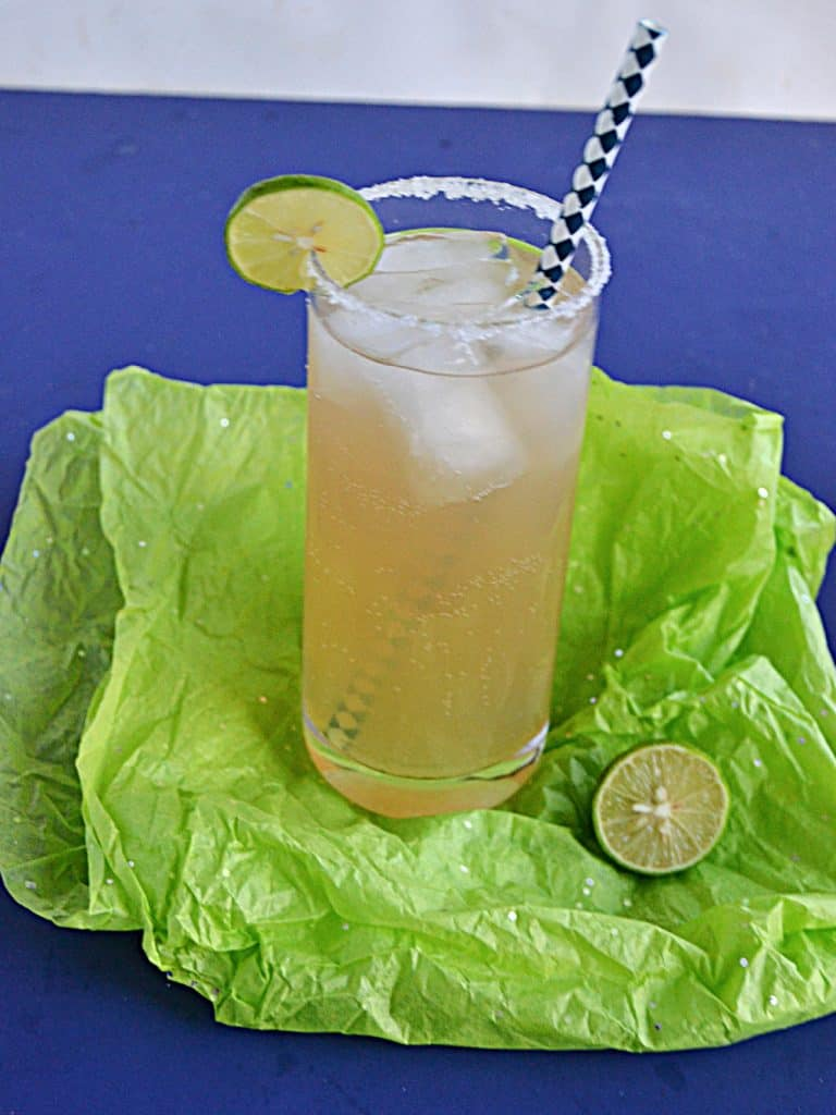 A glass of key lime margarita on the rocks with a lime wedge and salt on the rim and a straw in the glass.