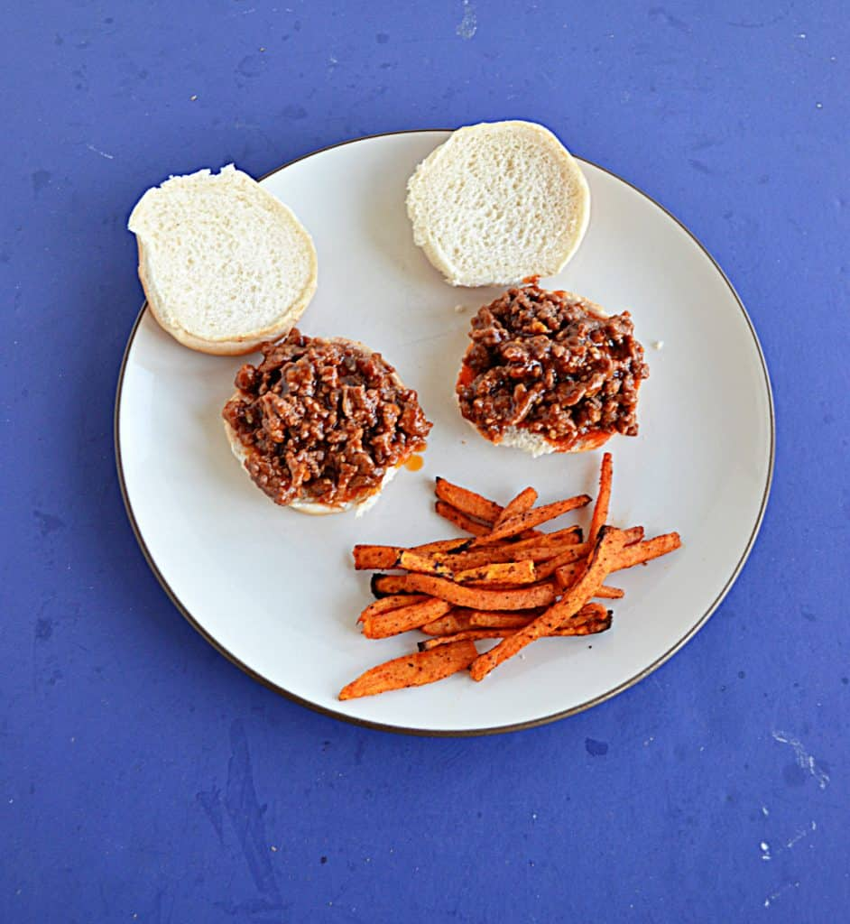 A plate with 2 Korean BBQ Sloppy Joes with a side of sweet potato fries.
