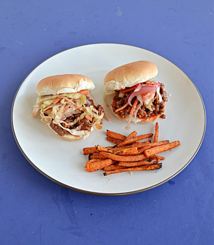 A plate with two Korean BBQ Sloppy Joes topped with pickled cabbage and carrots and a side of sweet potato fries.