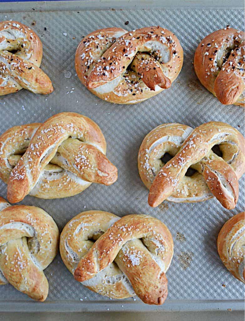 A close up view of golden brown soft pretzels on a baking sheet.
