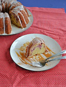 A slice of strawberry Bundt cake on a plate drizzled with caramel and two forks with the cut Bundt cake behind it.