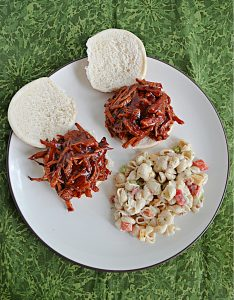 A plate with 2 pulled pork sandwiches and a big pile of pasta salad.