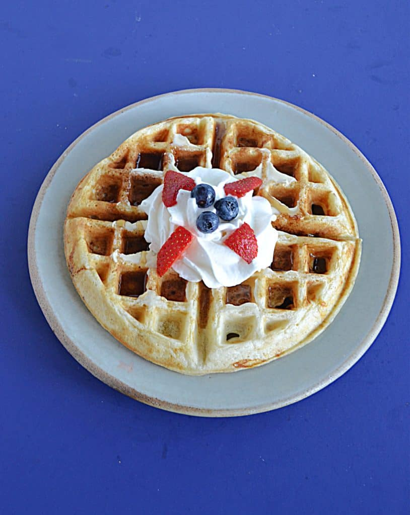 A plate with a Belgium waffle topped with whipped cream, blueberries, and strawberries.