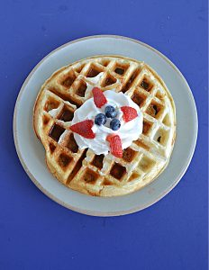 A top view of a Belgium Waffle topped with whipped cream and berries.