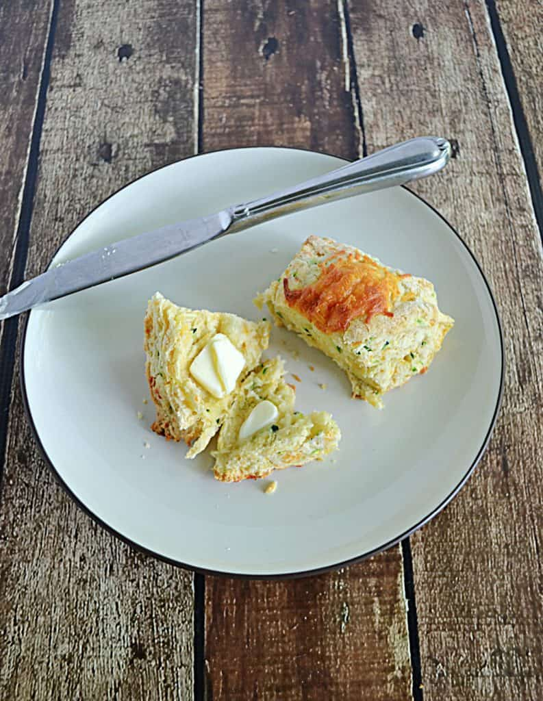 A plate with a zucchini cheddar scones cut in half and smeared with butter and a knife on the plate.