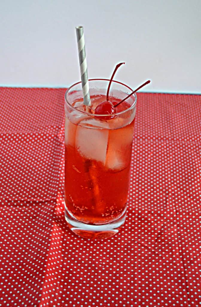 A glass filled with a Cherry Vanilla Bourbon Fizz with 2 cherries and a straw.