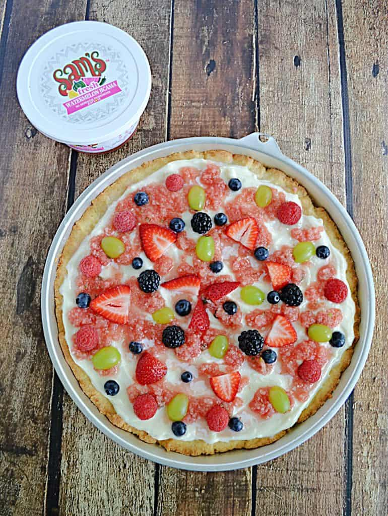 Top view of A fruit pizza topped with watermelon salsa and fresh fruit with a container of watermelon salsa behind it.