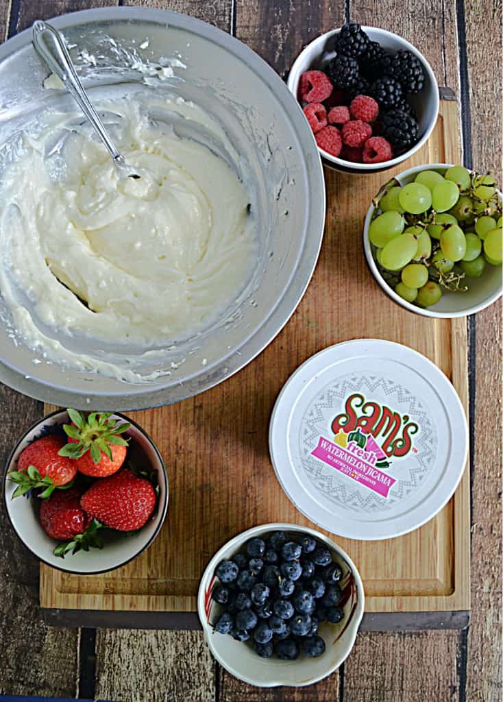 A cutting board topped with bowls of cream cheese frosting, strawberries, blueberries, grapes, blackberries, and watermelon salsa.