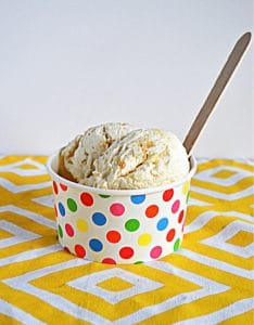 A rainbow dotted bowl with two scoops of Lemon Shortbread Ice Cream and a wooden spoon in it.