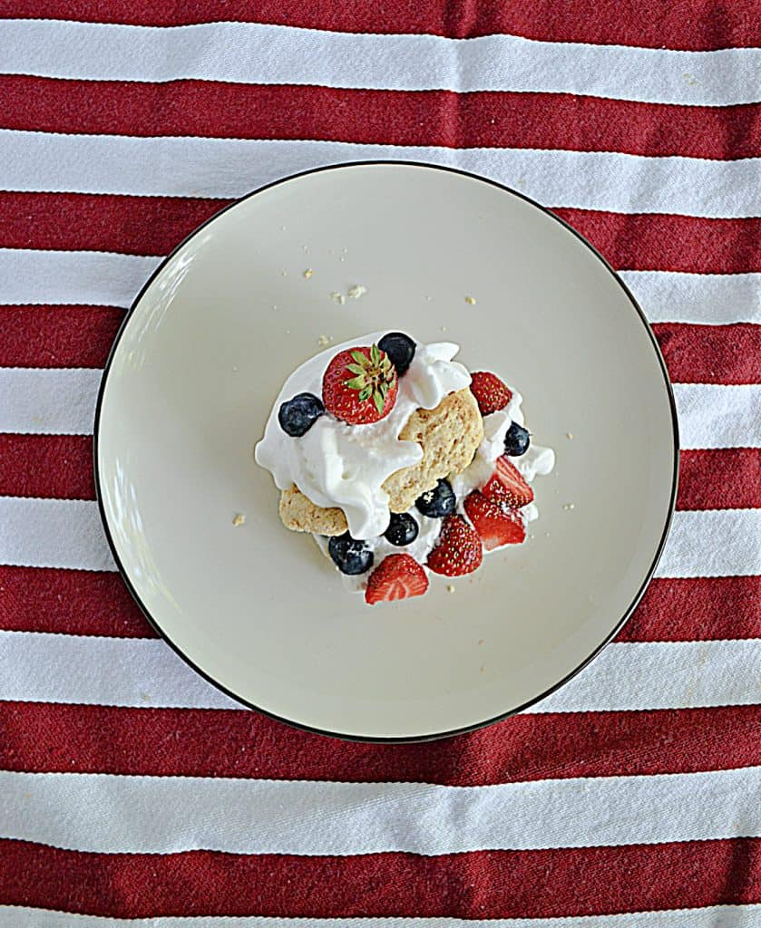 A plate stacked with biscuits, whipped cream, and berries.