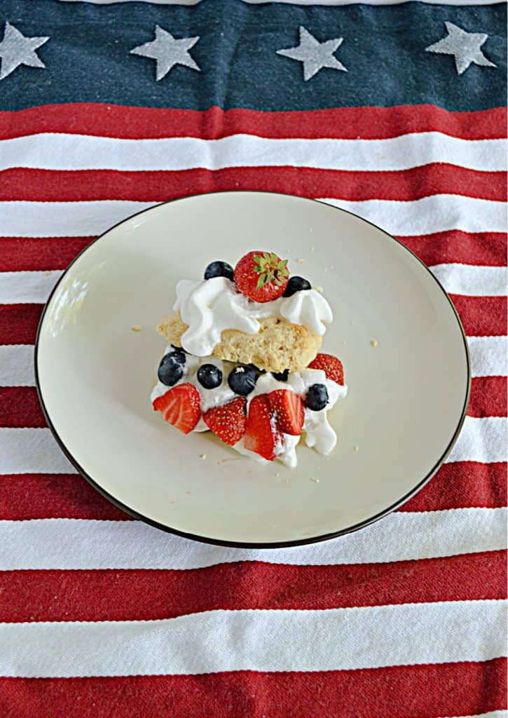 A front view of a shortcake made with biscuits, whipped cream, and berries.