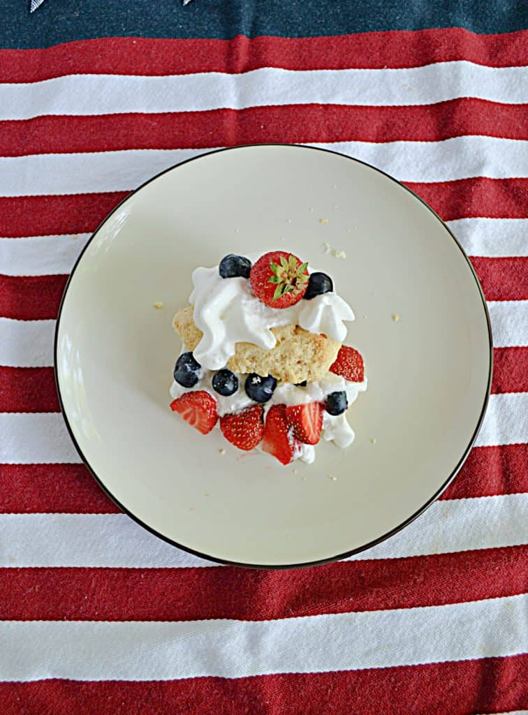 A plate with a shortcake made with sweet biscuits, whipped cream, strawberries, and blueberries.