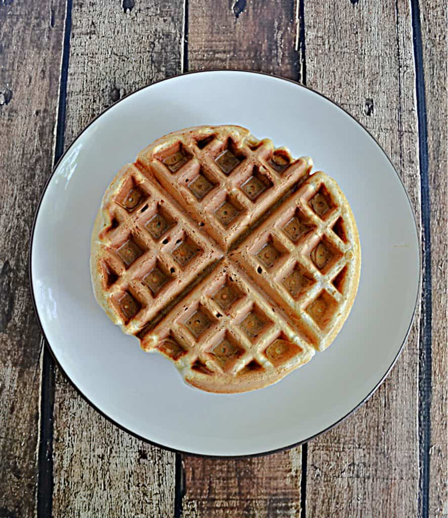 A Belgium waffle sitting on a plate.