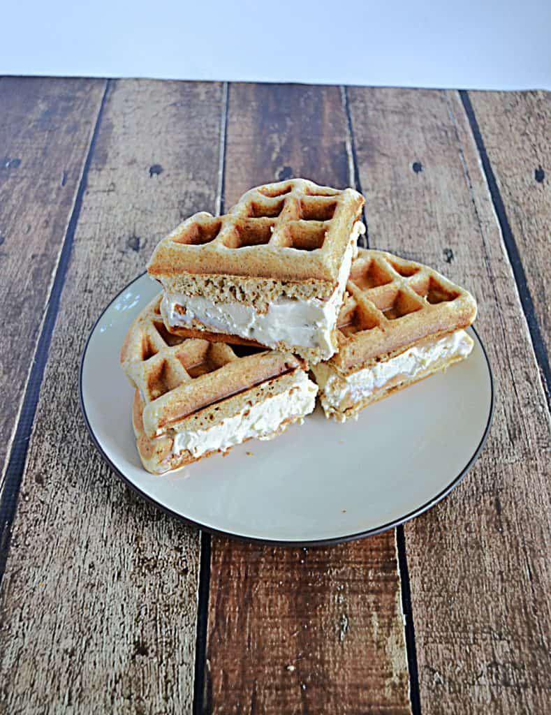 A plate with Waffle quarters filled with ice cream stacked on a plate.