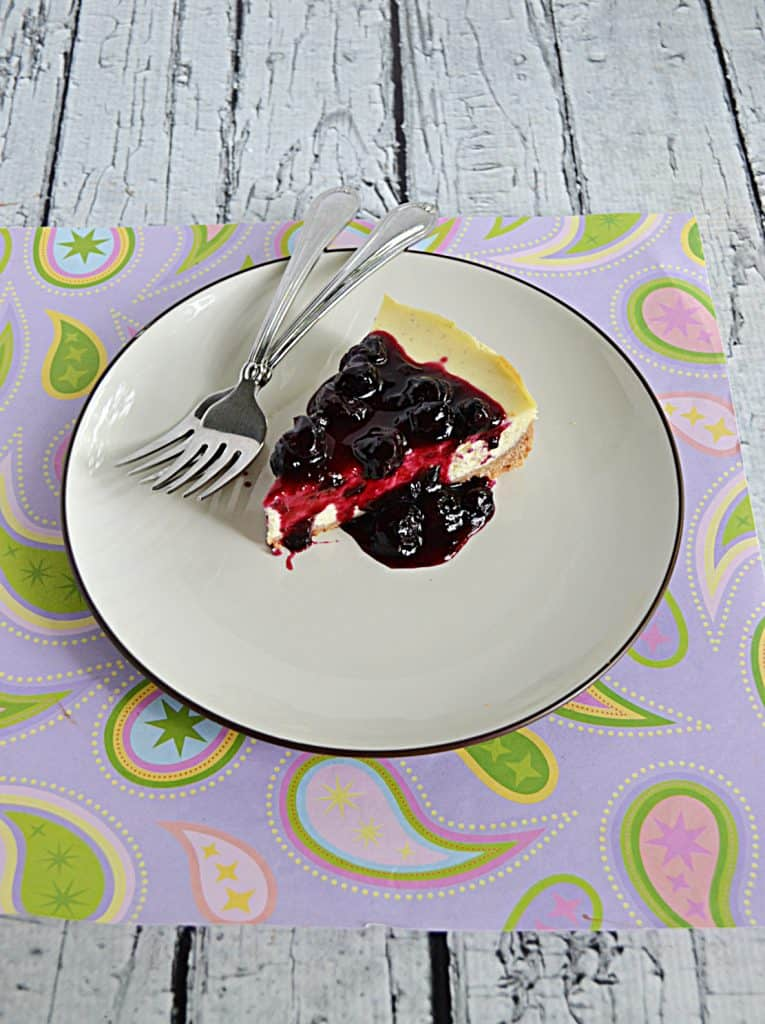 A slice of Vanilla Bean Cheesecake topped with blueberry compote with two forks on the plate.