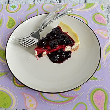 A plate with a slice of Vanilla Bean Cheesecake topped with blueberry compote with two forks on the plate.