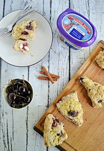 A cutting board with scones on it, a tub of butter, 3 cinnamon sticks, a bowl of cherries, and a plate with a scone and a fork on it.