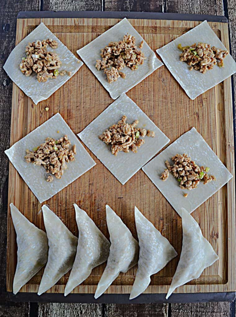 A cutting board with 6 stuffed chicken gyoza and six Chicken Gyoza that are laying on the wonton wrapper wready to be wrapped.